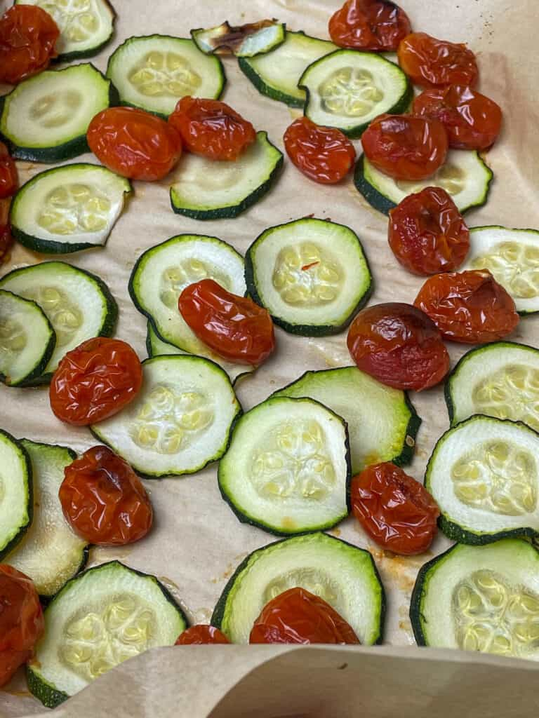 Slices of courgette and cherry tomatoes roasted and browned from the oven.