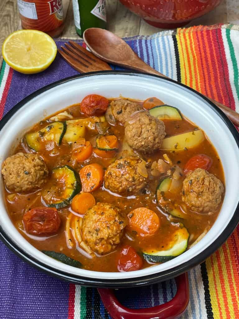 Bowl of Mexican meatball soup with lemon wedge, wooden fork and knife, and colourful stripy background.