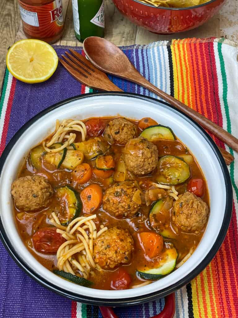 Mexican meatball soup served with hot sauce, lemon wedge, on a stripy mat.