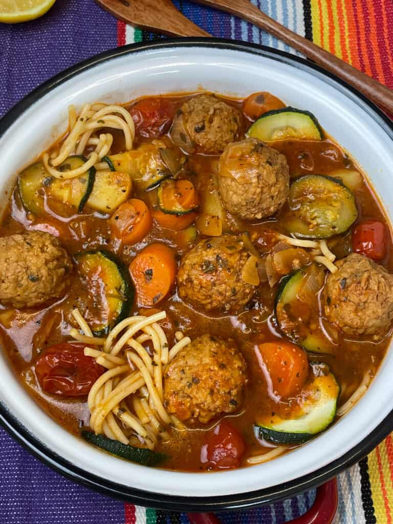close up of vegan Mexican meatball soup in white bowl with dark rim, colourful background.