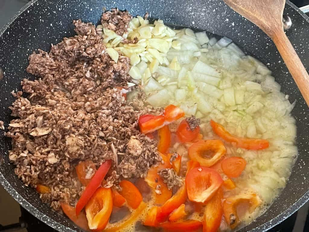 meat-free sausage pasta sauce ingredients in skillet with wooden spoon to side.