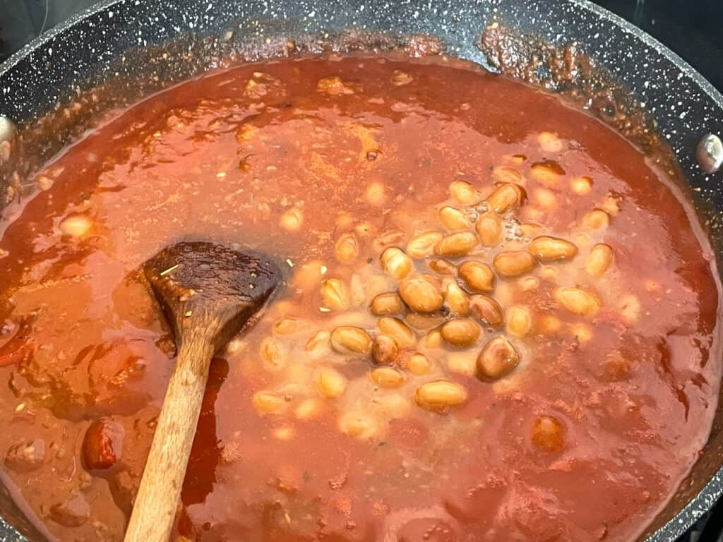 Pinto beans added to pasta sauce with wooden spoon.