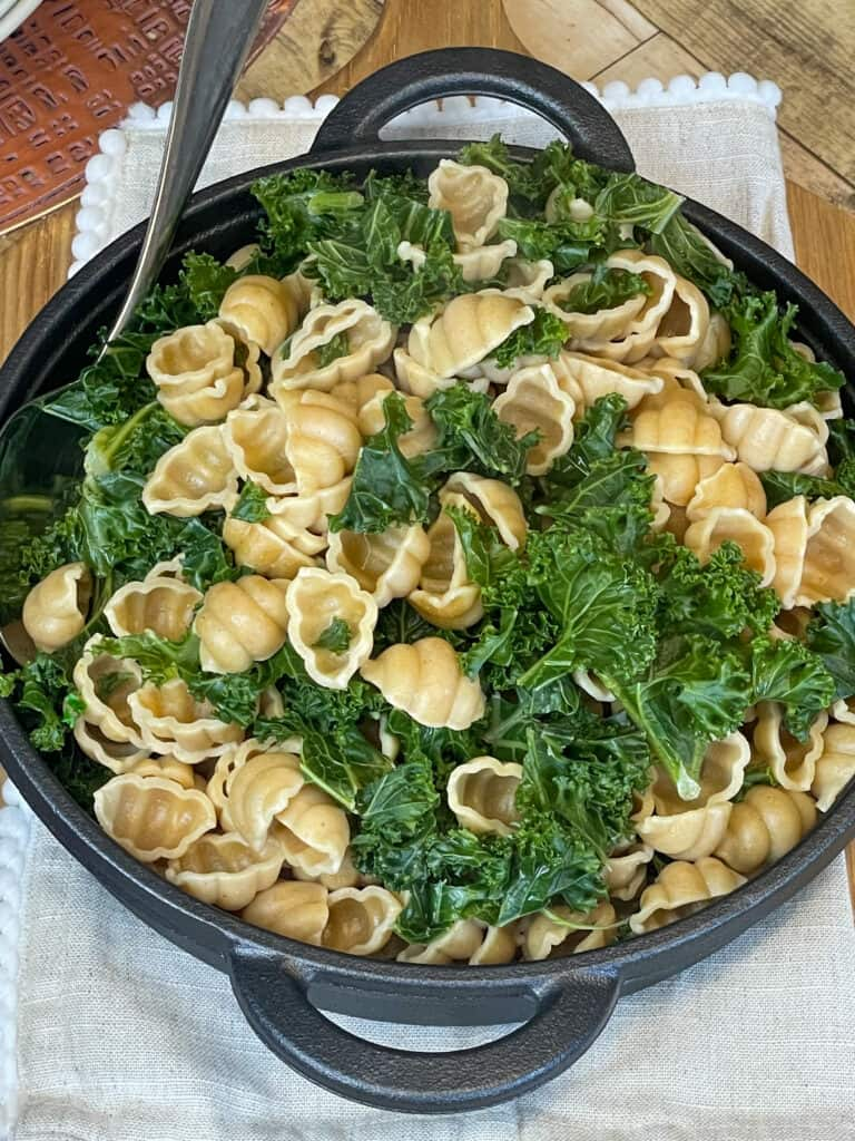 pasta shells and kale served in cast iron dish with silver serving spoon.