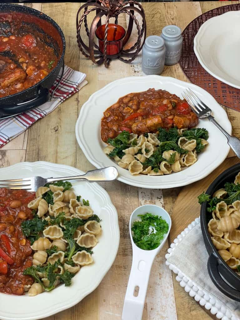 Two bowls of vegan sausage pasta with skillet to side, and wooden background, small dish of chopped herbs.