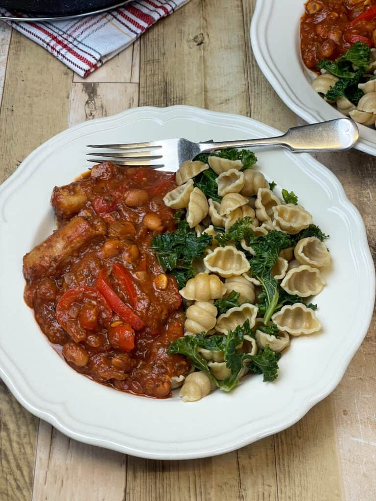 Sausage pasta served with wholemeal pasta shells and kale, wooden background.