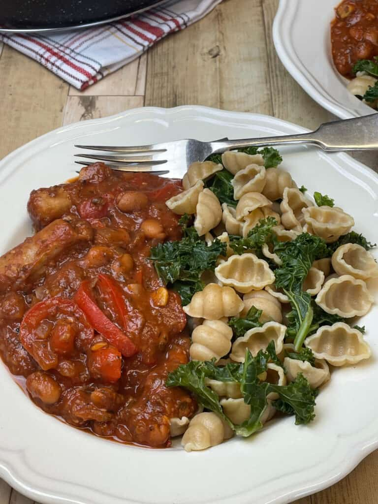 Bowl of vegan sausage pasta served with pasta shells and kale, silver fork and wood table background.